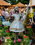 Bronze statue of Alice in Wonderland. Statue of Alice in Wonderland at the Hampton Court Flower show 2017 royalty free stock images