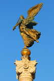 Bronze statue of ancient woman with wings and sword. With detailed pedestal, on blue sky, from Italy Royalty Free Stock Photo