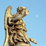 Bronze statue of an Angel, in Rome, with a pale moon in the sky. A marble statue of an Angel near Saint Angel Bridge in Rome, with a pale moon in the sky Royalty Free Stock Image