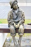 Bronze statue of  barefoot   child holding egg Royalty Free Stock Images