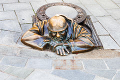 Bronze statue of Cumil the Peeper in Bratislav. BRATISLAVA, SLOVAKIA - SEPTEMBER 23, 2015: Bronze statue of Cumil the Peeper - Man Under a Manhole Cover. The Stock Photo