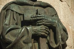 Bronze statue detail of priest hands holding a cross at Caceres. Bronze statue detail of priest hands holding a cross on the corner of the Santa Maria Cathedral stock photos