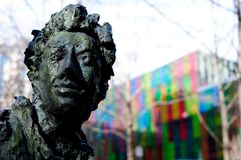 Bronze statue in downtown montreal. Colored reflection stock photos