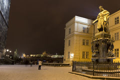 Bronze statue of the eleventh Czech King and Roman Emperor Charles IV. in night snowy Prague with Prague Castle near Charles Bridg Stock Photo