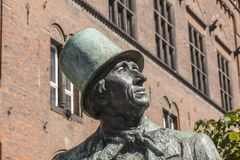 Bronze statue of famous danish fairy tale writer Hans Christian Andersen outside Copenhagen City Hall with blue sky background and stock photography