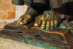 Bronze statue of feet over open book at Caceres. Bronze statue of feet over open book on the corner of the Santa Maria Cathedral at Caceres. A cute and charming royalty free stock images