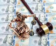 Bronze statue of Justice on the background of dollar bills Stock Image