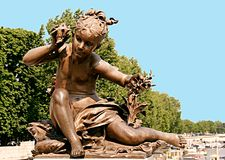 Bronze statue of a little girl hearing the sound of a conch and royalty free stock photography
