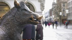 Bronze statue of wild boar in historical city center, tourists walking around. Stock footage stock video footage