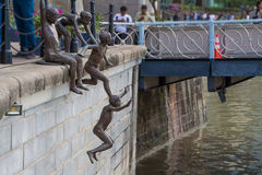 Bronze statues of kids jumping into river Stock Image