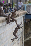 Bronze statues of kids jumping. Into river Royalty Free Stock Photos