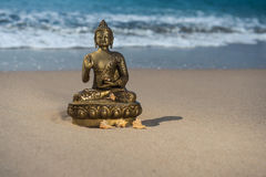 Bronze statuette Buddha on the beach with waves. Bronze statuette Buddha on the sandy beach with waves Stock Photography