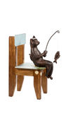 Cat goes fishing on a chair. Bronze statuette of a cat sitting on a wooden chair and fishing isolated on a white background royalty free stock photo