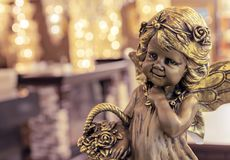 Bronze statuette of a girl with a flower basket on the background of bokeh royalty free stock photography