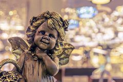 Bronze statuette of a girl with a flower basket on the background of bokeh stock photography