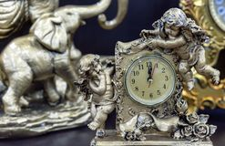 Bronze table clock with angels on a wooden table royalty free stock images