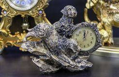 Bronze table clock with dogs on a wooden table royalty free stock images