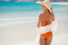 Bronze Tan Woman Sunbathing At Tropical Beach. A woman with a beautiful figure, brunette with long straight hair in orange bikini, in a large straw hat with a Stock Photography