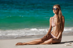 Bronze-Tan Woman Sunbathing At Tropical-Strand stockfoto