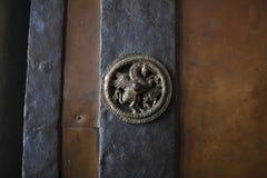 Bronze unicorn on a wooden door. royalty free stock photo