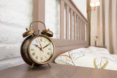 Bronze vintage alarm clock. Vintage alarm clock on a wooden table in a hotel room Royalty Free Stock Photo