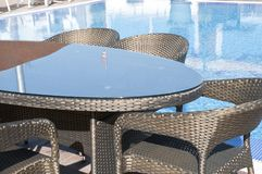 Bronze wicker furniture sets by the pool. Table and bronze chairs closeup view stock image