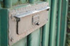 Bronzebriefkasten auf grüner metallischer Tür Lizenzfreies Stockfoto