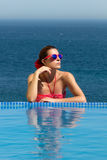 Bronzed Beauty. Poolside Girl. Woman in Red. Young brunette woman in bikini, flower in hair and red glasses, sunbathing on the edge of the infinity pool Royalty Free Stock Photography