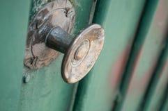 Bronzegriff auf grüner metallischer Tür Stockbild