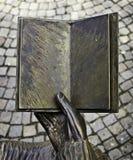 Bronzehand mit Buch Stockfotos