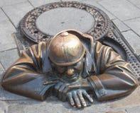 Bronzemann, der vom Abwasserkanal auftaucht Stockfoto
