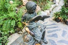 Bronzeskulptur des Jungen mit Buch im Garten Lizenzfreie Stockfotos