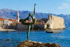 Bronzeskulptur des Mädchens gegen alte Stadt von Budva Lizenzfreie Stockfotografie