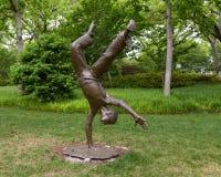 Bronzeskulptur eines Kindes, das ein Wagenrad durch Gary Price an Dallas Arboretum und am botanischen Garten tut lizenzfreies stockfoto