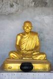 Bronzestatue des sitzenden Mönchs mit grauem konkretem Hintergrund stockfoto
