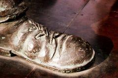 Bronzestatuenschuh mit Spitzeen auf rötlich braunem Metallhintergrund Lizenzfreies Stockbild