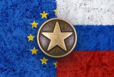 Bronzestern auf Europäischer Gemeinschaft und russische Flaggen im Hintergrund Stockfoto