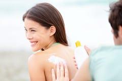 Bronzez la lotion/protection solaire - jeune couple sur la plage photos stock