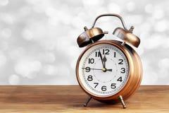 Bronzez un rétro un réveil sur le fond blanc de bokeh Image libre de droits
