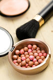 Bronzing pearls and makeup brush Stock Photography
