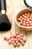 Bronzing pearls and makeup brush Stock Photos