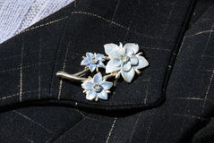 Brooch. On a business female suit of dark blue color royalty free stock photography
