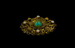 Brooch. Gold brooch isolated on black background Royalty Free Stock Photography