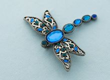 Brooch in the form of dragonfly. On blue background Royalty Free Stock Photography