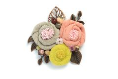 Brooch handmade from a fabric consisting of three flowers of gray, pink and yellow colors Stock Photo