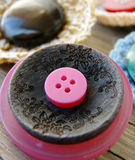 Brooches with buttons. On old wooden table Royalty Free Stock Photography