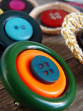 Brooches with buttons. On old wooden table Stock Images