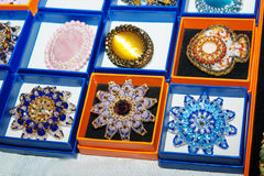 Brooches made of glass and amber at the exhibition Stock Photos