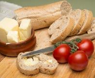 Brood en boter/Heerlijke organische eigengemaakte brood en boter met rijpe tomaten op houten raad Stock Foto