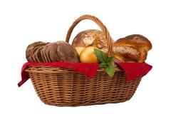 Brood en broodjes in rieten die mand op wit wordt geïsoleerd Stock Foto